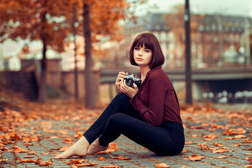 Обои Модель Мария с фотоаппаратом сидит на дороге с осенними листьями, фотограф Lods Franck