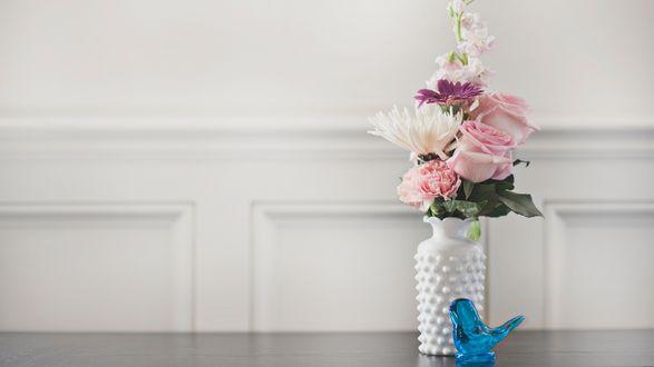 Обои Букет цветов в вазе и фигурка птицы на столе
