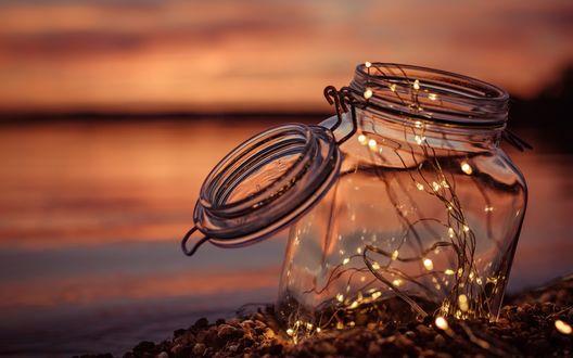 Обои Стеклянная баночка с гирляндой на фоне заката