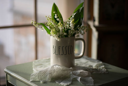 Обои Ландыши в чашке на столе с салфеткой, фотограф Julie Jablonski