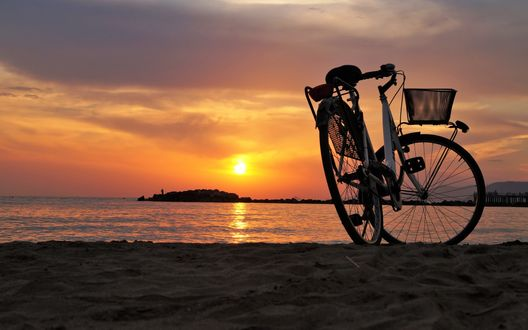 Обои Велосипед стоит у моря на фоне заката