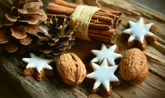 Обои Шишки, палочки корицы, орех и печенье на столе
