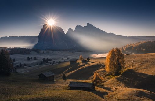 Обои Солнце над вершиной горы освещает долину с домиками, фотограф Marco Grassi
