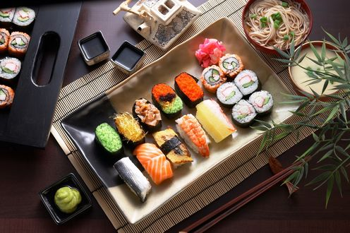 Обои Японская кухня: ассорти из рисовых суши роллов рыбой и черной и красной икры, рядом соус, васаби, маринованный имбирь, лапша и палочки для еды