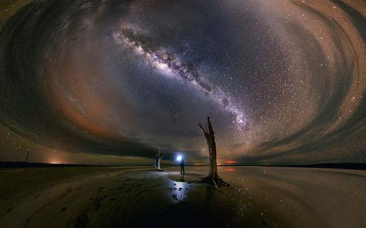 Обои Мужчина с фонарем на фоне млечного пути в звездном небе, уходящего в бесконечность с землей