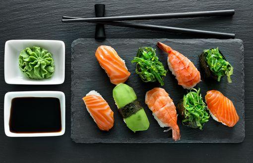 Обои Японская кухня: ассорти из рисовых суши роллов рыбой, креветками и огурцом, рядом соус, васаби и палочки для еды