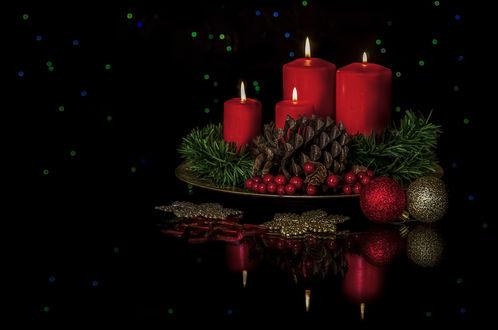 Обои Зажженные свечи, ягоды, елочные:ветка, шишка и украшения на черном отражающемся фоне с бликами