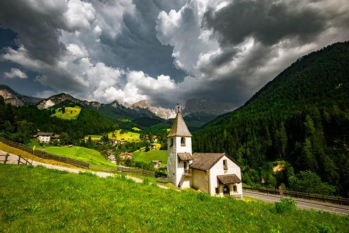 Обои Часовня у дороги на фоне деревушки между горами под облачным небом, фотограф sardegna orange