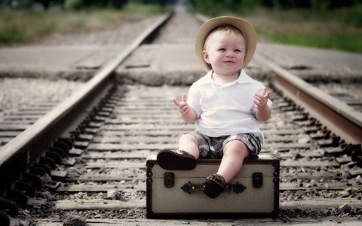 Обои Мальчик сидит на чемодане между рельс