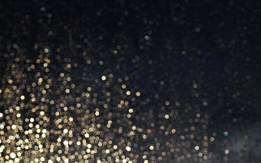 Обои Множество золотистых блесток на размытом сером фоне