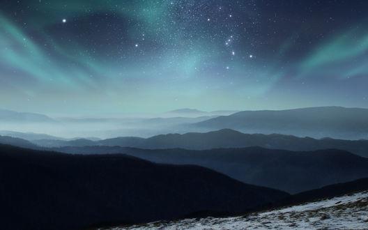 Обои Северное сияние в звездном небе над туманными заснеженными горами