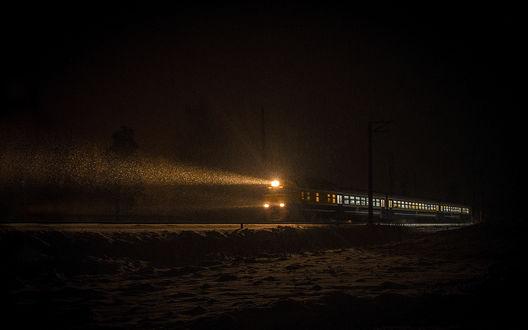Обои Поезд едет по заснеженной дороге, освещая путь сквозь пургу в ночи