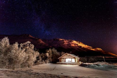 Обои Одинокий домик ночью на фоне зимней природы, гор и звездного неба