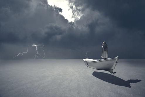 Обои Девушка в лодке парит перед мрачным облачным небом, фотограф Оzkan Durakoglu