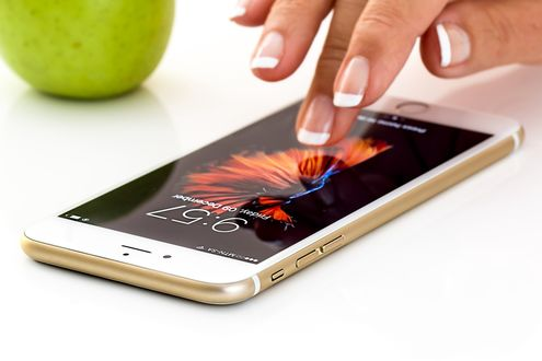Обои Рука девушка над смартфоном и зеленое яблоко