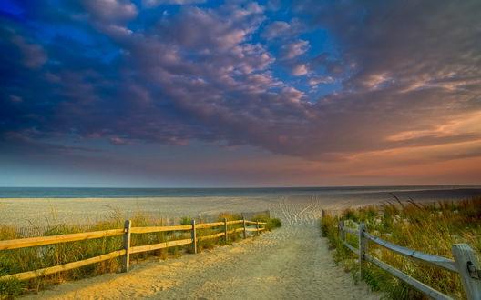 Обои Песчаная дорога с заборами, ведущая на пляж в пасмурный день