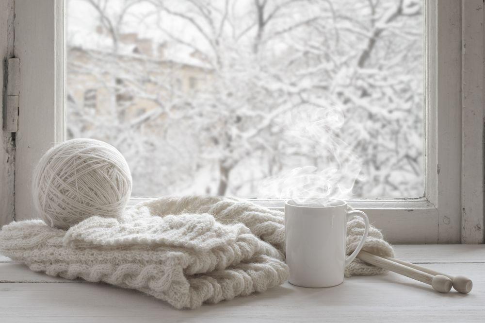 Обои для рабочего стола Вязание и чашка с горячим чаем стоит на окне, за которым видны заснеженные деревья