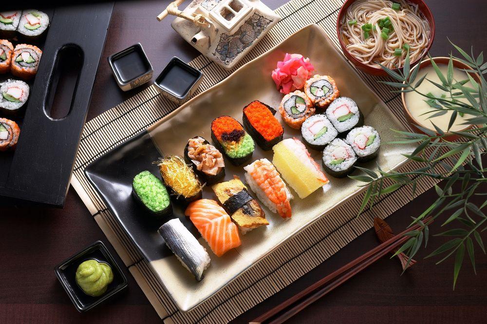 Обои Японская кухня: ассорти из рисовых суши роллов рыбой и черной и  красной икры, рядом соус, васаби, маринованный имбирь, лапша и палочки для  еды на рабочий стол