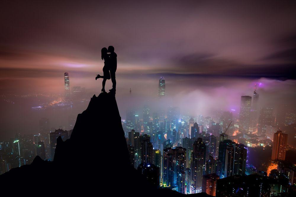 Обои для рабочего стола Влюбленные стоят на вершине горы на фоне ночного города в огнях