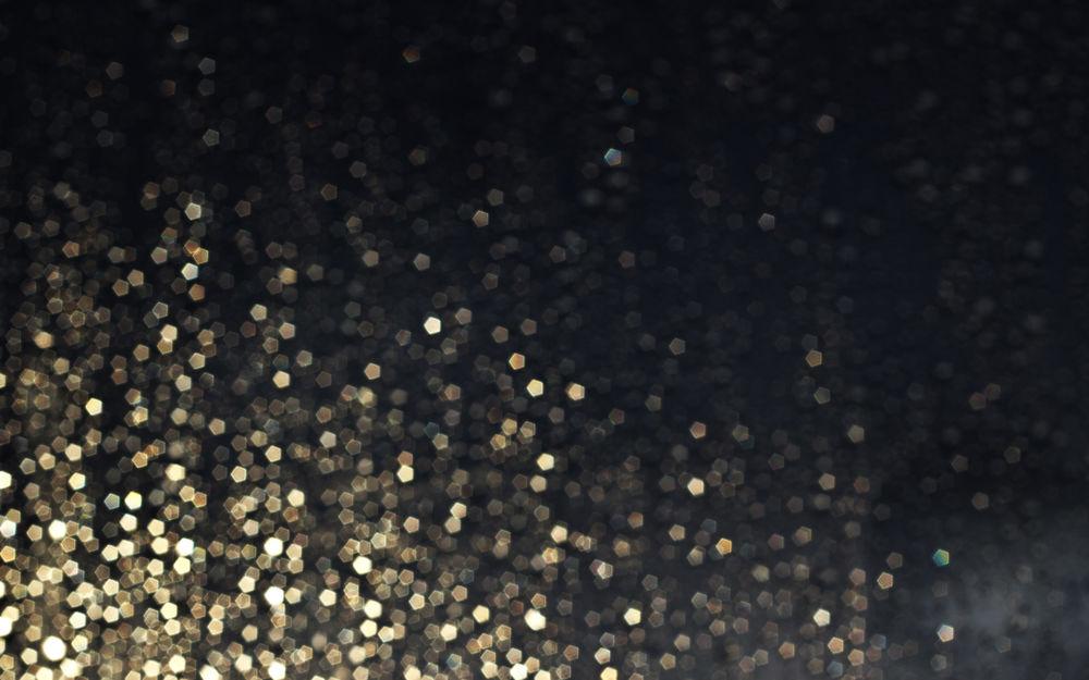 Обои для рабочего стола Множество золотистых блесток на размытом сером фоне