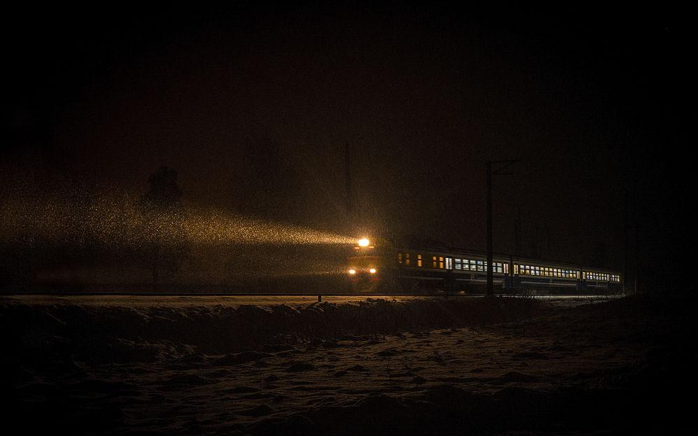 Обои для рабочего стола Поезд едет по заснеженной дороге, освещая путь сквозь пургу в ночи