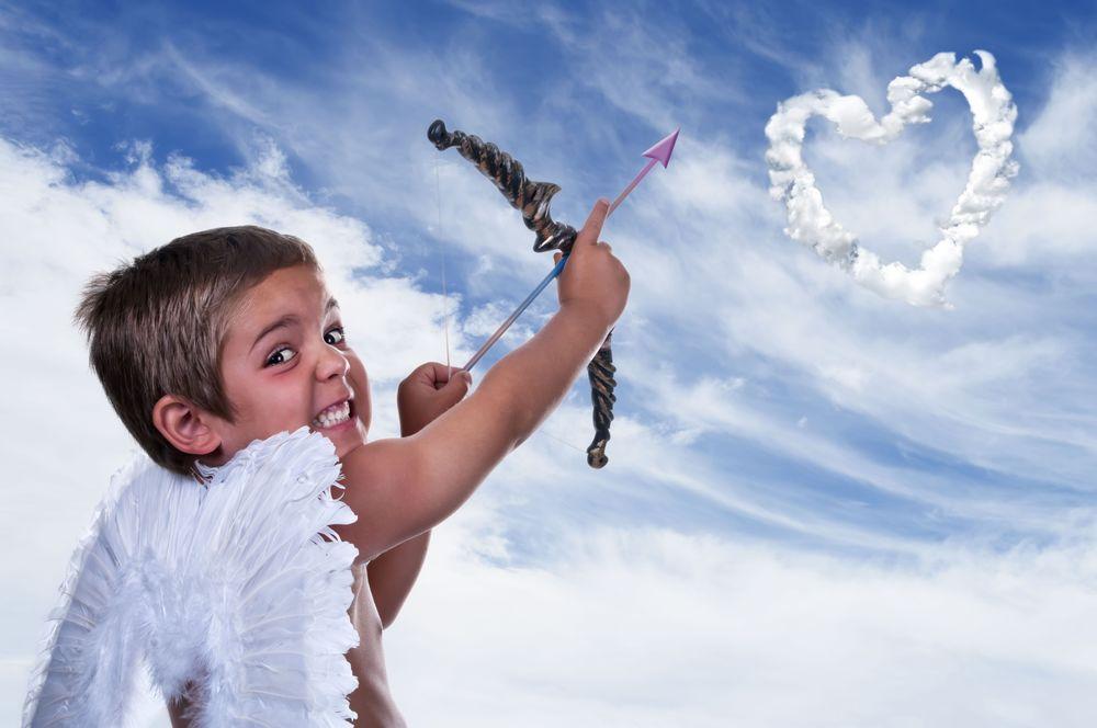 Обои для рабочего стола Шаловливый мальчик, одетый купидоном, целится из лука в небо, стараясь попасть в изображение сердечка