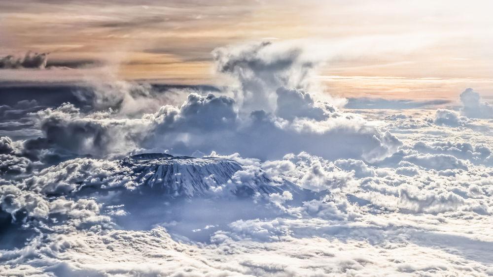 Обои для рабочего стола Вулкан Килиманджаро / Kilimanjaro среди облаков, Танзания / Tanzania, фотограф Cyril Blanchard