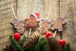 Обои Новогодние карамельные леденцы на палочке, шишки и еловые веточки на деревянной поверхности