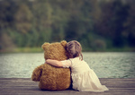 Обои Девочка сидит в обнимку с игрушечным мишкой на деревянном настиле, у воды, спиной к камере, by Matildamami