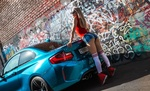 Обои Стройная блондинка стоит, прислонившись к авто на фоне забора с граффити