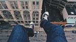 Обои Человек сидит на краю крыши дома спустив ноги