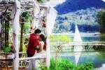 Обои Жених с невестой в увитой цветами беседке, на заднем плане река с парусной яхтой, Вьетнам