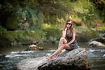 Обои Девушка в легком платьице сидит на скале у берега реки, на размытом фоне деревьев, by A. Stoianow
