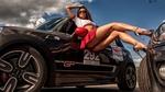Обои Модель демонстрирует ножки, устроившись меж двух авто, на фоне неба, фотограф Олег Климин