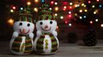 Обои Два игрушечных снеговичка и шишки на фоне разноцветных огоньков