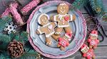 Обои Семья пряничных человечков, приготовленных для украшения елки, на тарелке среди еловых веток