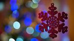 Обои Красная снежинка висит на фоне бликов