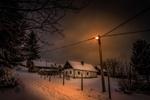Обои Заснеженные дома на улице, освещенной светом фонарей зимней ночью