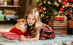 Обои Улыбающаяся светловолосая девочка в обнимку с собакой лежит под новогодней елкой с подарками