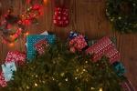 Обои Ножки в красных новогодних носочках со снежинками перед наряженной елкой с подарками под ней, рядом лежит венок и светящаяся разноцветными огоньками гирлянда