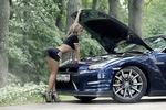 Обои Девушка смотрит на моторный отсек Nissan GT-R / Ниссан ГТ-Р на дороге у леса