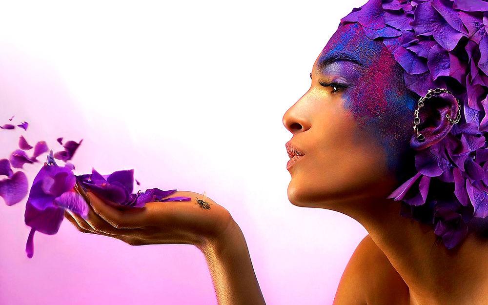 Обои для рабочего стола Девушка с композицией, из лепестков и краски, на лице и голове, сдувает лепестки с ладони, на которой сидит пчела