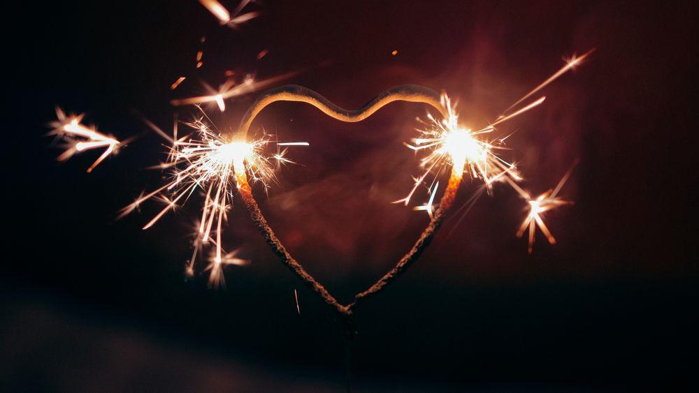 Обои для рабочего стола Бенгальские огни в форме сердца с искрами на фоне ночного неба