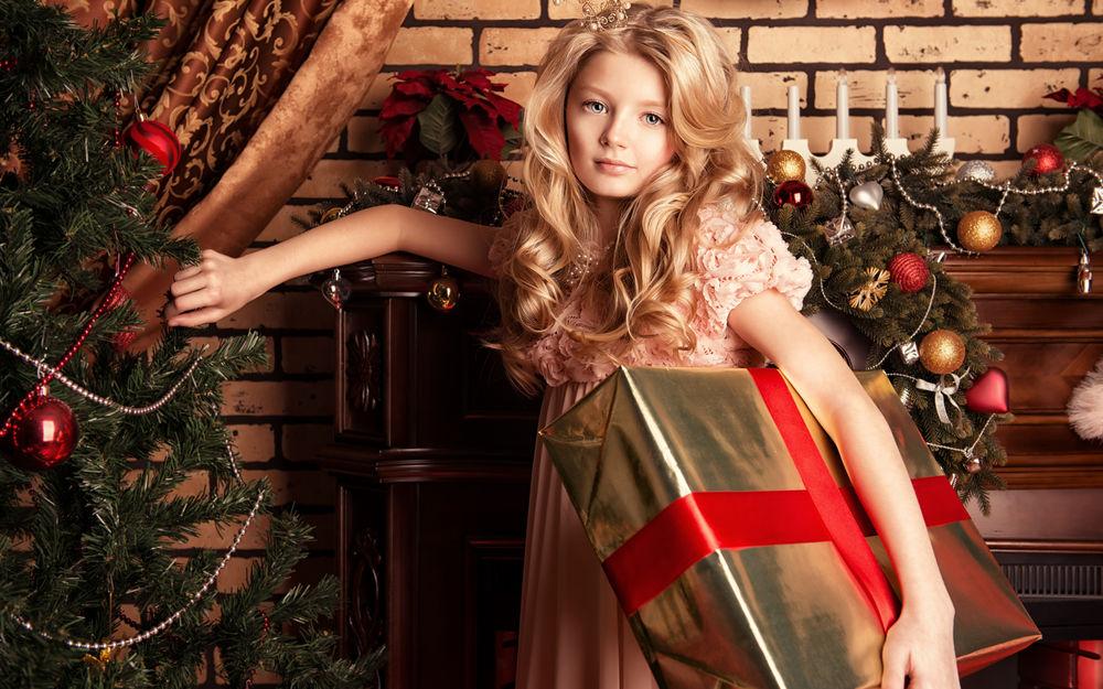 Обои для рабочего стола Светловолосая девочка в наряде принцессы с большой подарочной коробкой на фоне новогодних декораций