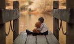 Обои Девочка, обнимая игрушечного мишку, сидит на мостике, фотограф Salih GОKDUMAN