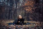 Обои Девушка в черном платье лежит на земле, в осеннем парке, фотограф George Prapas