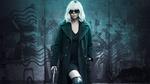 Обои Шарлиз Терон / Charlize Theron в роли Лоррейн Бротон из фильма Взрывная блондинка / Atomic Blonde в черных очках и пальто стоит с пистолетом в руке