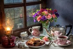 Обои Стол накрыт для чаепития со свежеиспеченным кексом и стоит букет роз в вазе, все освещено керосиновой лампой, за окном моросит дождь