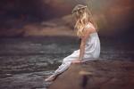 Обои Белокурая девочка в белом сарафане, с венком на голове, сидит на камне, свесив ноги в воду, by JULIA ALTORK
