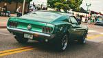 Обои Темно-зеленый Mustang на дороге небольшого городка